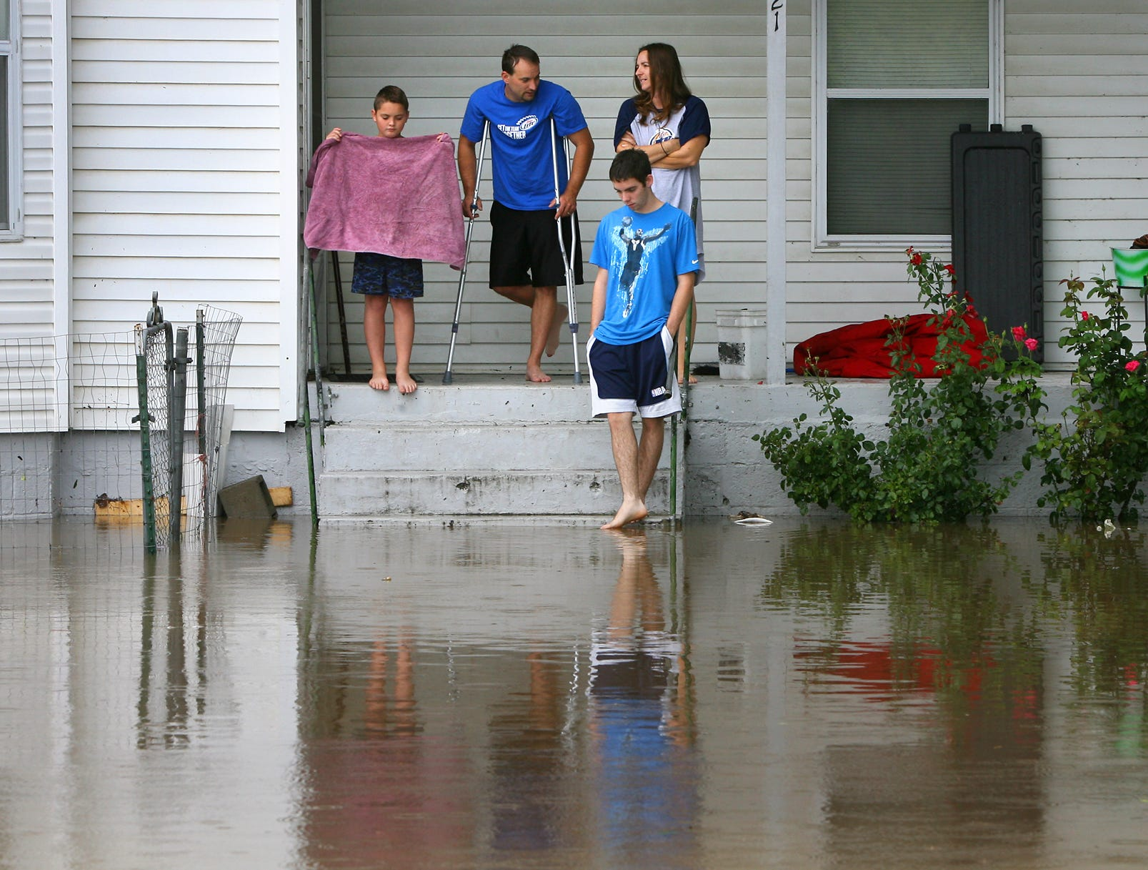 The Russell family watches as Little Piney Creek overflowed its banks on Aug. 7 in downtown Newburg, Mo. One person was killed as heavy rains caused flash flooding and closed sections of Interstate 44 and U.S. 63.