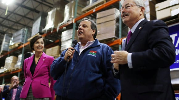 Gov. Chris Christie, center, flanked by Iowa Lt. Gov. Kim Reynolds and Iowa Gov. Terry Branstad, speaks during a get-out-the-vote rally, Thursday, Oct. 30, 2014 at the Winegard Company in Burlington, Iowa. Christie is back in Iowa today, this time campaigning on his own behalf. (AP Photo/The Hawk Eye, John Lovretta)
