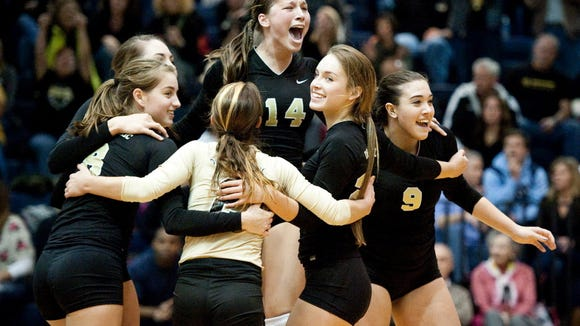 Delone Catholic players celebrate around Maddie Comly (14) after scoring the winning point in the fifth game against Berks Catholic in the PIAA District 3 girls' volleyball title match last year at Dallastown Area High School. (GAMETIMEPA.COM -- FILE)