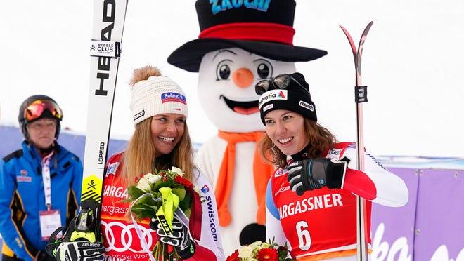 First placed Switzerland's Corinne Suter, left, and third placed Switzerland's Michelle Gisin pose for photos at the end of an alpine ski, women's World Cup downhill, in Altenmarkt-Zauchensee, Austria, Saturday, Jan. 11, 2020.