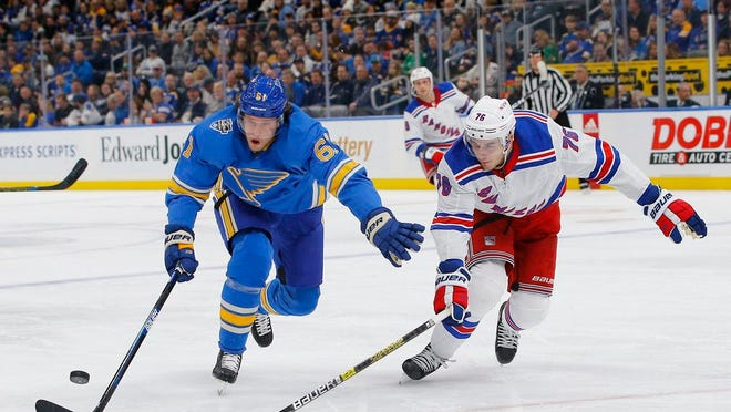 St. Louis Blues' Jacob de la Rose, left, of Sweden, and New York Rangers' Brady Skjei reach for a loose puck during the second period of an NHL hockey game Saturday, Jan. 11, 2020, in St. Louis.