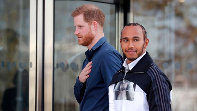 Britain's Prince Harry, the Duke of Sussex, arrives with Formula One world champion Lewis Hamilton, right, to officially open the Silverstone Experience, a new immersive museum about British motor racing, in Towcester, Friday, March 6, 2020.