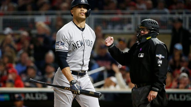 New York Yankees' Giancarlo Stanton walks back to the dugout after striking out during the second inning in Game 3 of a baseball American League Division Series against the Minnesota Twins, Monday, Oct. 7, 2019, in Minneapolis.