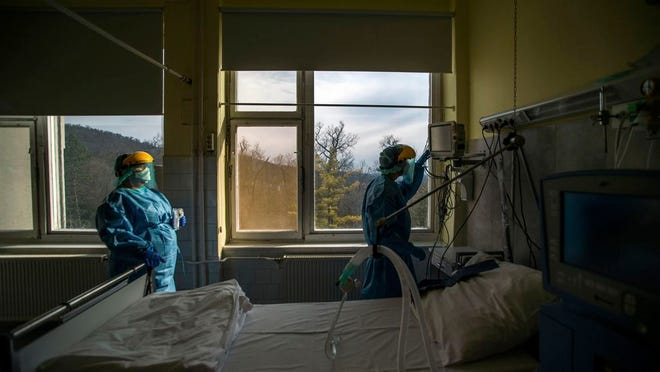 FILE - In this March 24, 2020, file photo, medical staff members check a ventilator in protective suits at the care unit for the new COVID-19 infected patients inside the Koranyi National Institute of Pulmonology in Budapest. As health officials around the world push to get more ventilators to treat coronavirus patients, some doctors are moving away from using the breathing machines when they can.