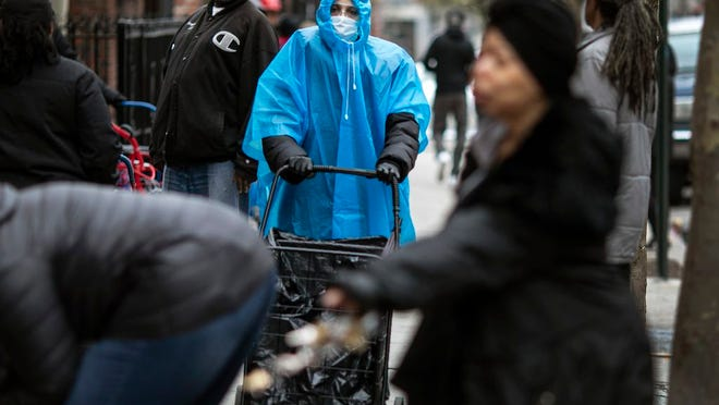 A woman dressed in a poncho, face mask and protective eyewear pushes her grocery cart in the Bedford-Stuyvesant neighborhood of Brooklyn, New York, on Friday, March 20, 2020. New York Gov. Andrew Cuomo is ordering all workers in non-essential businesses to stay home and banning gatherings statewide. Nonessential gatherings of individuals of any size or for any reason are canceled or postponed.