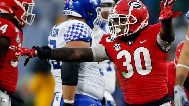 From Oct. 19, 2019, Georgia inside linebacker Tae Crowder (30) celebrates after bringing down Kentucky quarterback Lynn Bowden Jr. during the first half of an NCAA college football game in Athens, Ga. Crowder is going to have to settle for being Mr. Irrelevant without the frills for now. Still, the Georgia linebacker is just happy being picked by the New York Giants in the NFL draft.