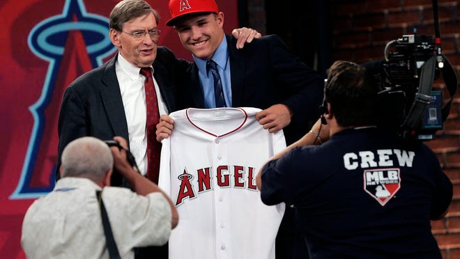 From June 9, 2009, Baseball Commissioner Bud Selig poses with Mike Trout, an outfielder from New Jersey's Millville High School, who was picked 25th by the Los Angeles Angels in the baseball draft in Secaucus, N.J. Baseball's amateur draft this week will look much different because of the coronavirus pandemic, and more permanent changes could be coming soon.