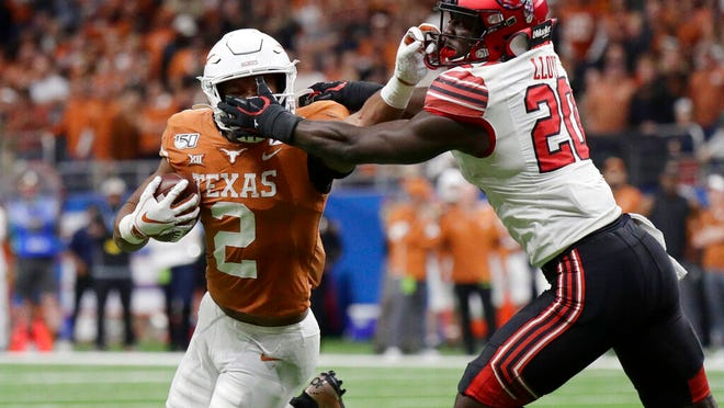 Texas running back Roschon Johnson (2) has his face mask grabbed by Utah linebacker Devin Lloyd (20) during the second half of the Alamo Bowl NCAA college football game in San Antonio, Tuesday, Dec. 31, 2019.
