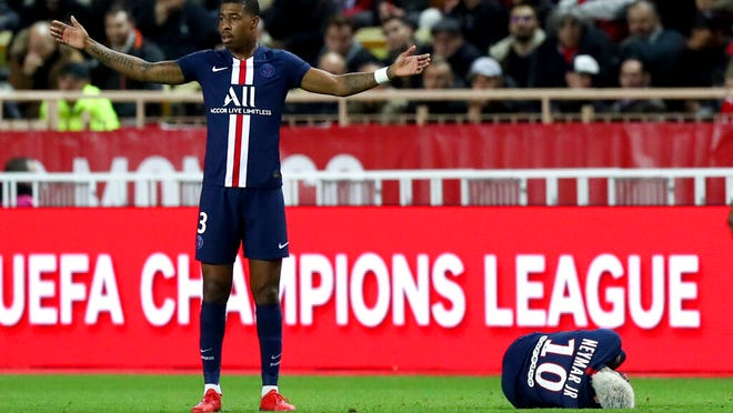 PSG's Presnel Kimpembe reacts as PSG's Neymar lays on the turf during the French League One soccer match between Monaco and Paris Saint-Germain at the Louis II stadium in Monaco, Wednesday, Jan. 15, 2019.