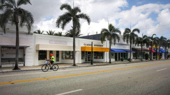 A lone cyclist pedals along South County Road between Royal Palm Way and Brazilian Avenue on Tuesday.  The usually bustling business district is empty as a result of the coronavirus pandemic.