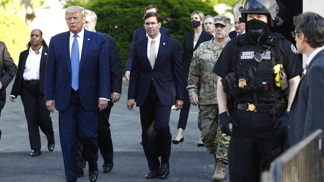 WASHINGTON -- U.S. Defense Secretary Mark Esper (right) walks with President Donald Trump as he departs the White House to visit outside St. John's Church on June 1. Esper later distanced himself from Trump's comments about using U.S. military personnel to quell citizen protests.