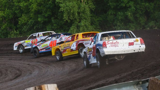 The IMCA Stock Cars race into turn out during heat race action at Norman County Raceway on Thursday.