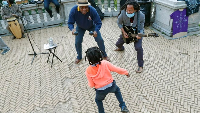 In this Tuesday, June 16, 2020, photo, musician Alix Julien, above, center, encourages 6-year-old Nova Sankara to dance as Alegba Jahyile, right, leads the band Alegba and Friends in a nightly concert at Brooklyn's Prospect Park boathouse in New York. In pre-COVID-19 days, the band performed in local bars and restaurants. But since the pandemic, indoor restaurant dining has been suspended, so the group has taken their music outdoors by the water's edge where they've developed a loyal following of regulars. Sankara's father is a professional dancer.