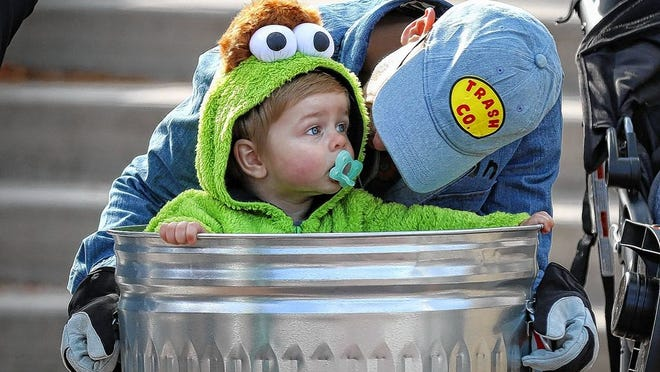 Duncan Podolski, 1, of Hilliard, wearing an Oscar the Grouch costume and prop, attended the Old Hilliard Halloween Haunt with his father, James, on Oct. 19, 2019. Hilliard leaders say they intend to have Beggars Night this year during the COVID-19 coronavirus, scheduling it for 6 to 8 p.m. Oct. 29.