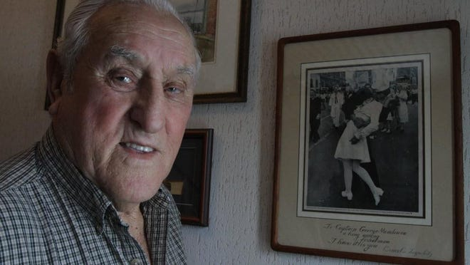 """George Mendonsa posed with """"The Kissing Sailor"""" at his Middletown home in 2013."""