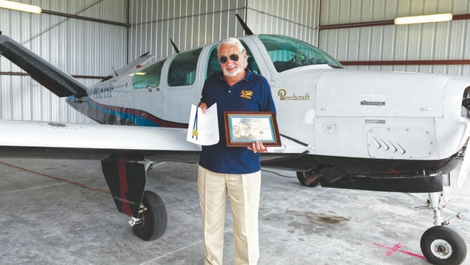 Captain Robert Britton with The Wright Brothers Master Pilot Award and Blue ribbon file in front of his 1974 Beechcraft Bonanza.