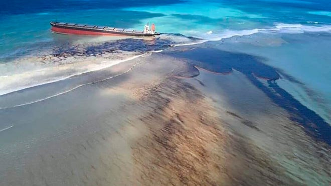 """This photo taken and provided by Georges de La Tremoille of Mu Press shows oil leaking from the MV Wakashio, a bulk carrier ship that recently ran aground off the southeast coast of Mauritius, Friday, Aug. 7, 2020. The Indian Ocean island of Mauritius declared a """"state of environmental emergency"""" late Friday after a Japanese-owned ship that ran aground offshore days ago began spilling tons of fuel."""