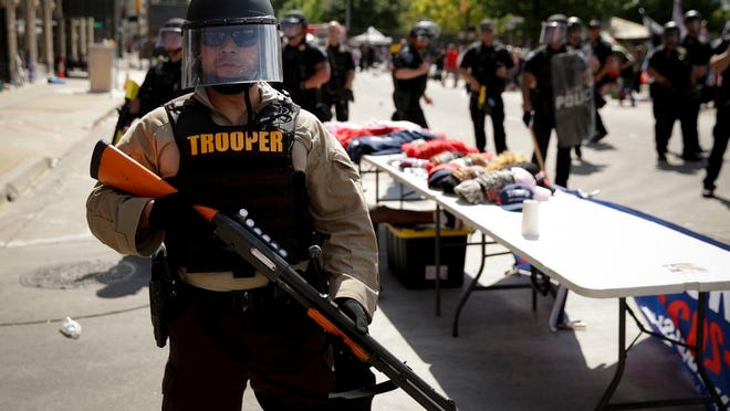 """In this June 20, 2020, file photo a trooper stands outside the BOK Center where President Trump will hold a campaign rally in Tulsa, Okla. In law enforcement, they're referred to as """"non-lethal"""" tools for crowd control: Rubber bullets. Pepper spray. Batons. Flash-bangs. But the now-familiar scenes of U.S. police officers in riot gear clashing with protesters at Lafayette Park in Washington and elsewhere around the country have police critics charging that the weaponry too often escalates tensions and hurts innocent people."""