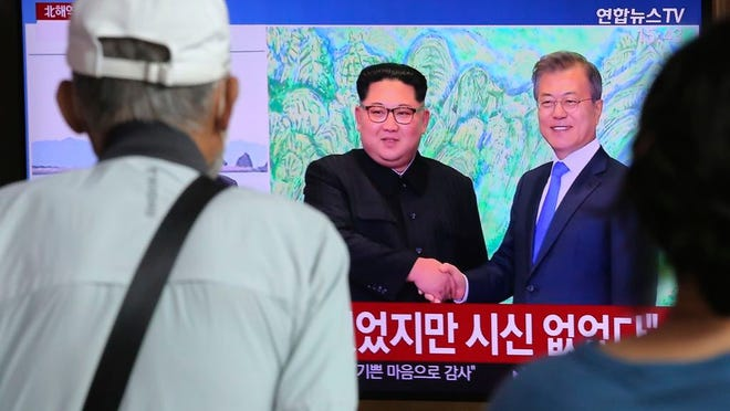 """People watch a TV showing a file image of North Korean leader Kim Jong Un, left, and South Korean President Moon Jae-in during a news program at the Seoul Railway Station in Seoul, South Korea, Friday, Sept. 25, 2020. North Korean leader Kim apologized Friday over the killing of a South Korea official near the rivals' disputed sea boundary, saying he's """"very sorry"""" about the incident he called unexpected and unfortunate, South Korean officials said."""
