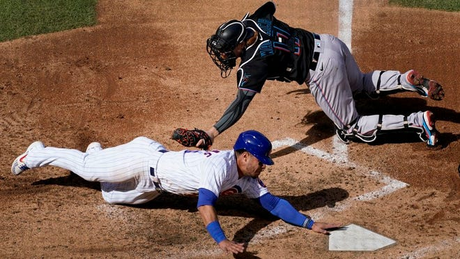 Chicago Cubs' Willson Contreras, bottom, is tagged out before reaching home by Miami Marlins catcher Chad Wallach (17) during the fourth inning of Friday's game.