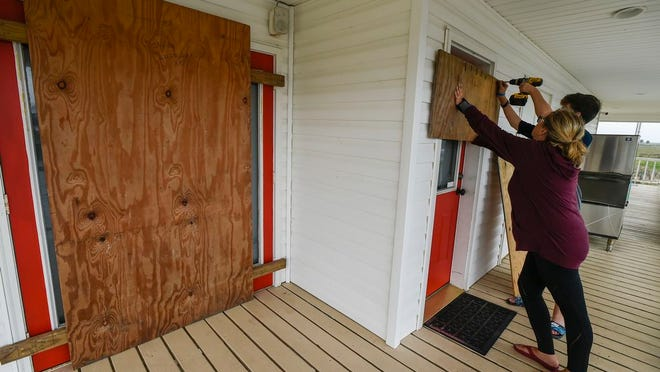 Residents Mamie Russo and her son Cole attach wood to their front door while preparing for Hurricane Delta on Thursday, Oct. 8, 2020, in Cypremort Point, La.