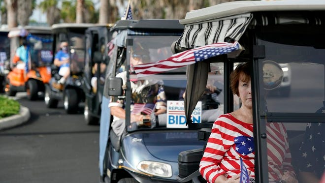 Carts line up before a parade of over 300 golf carts supporting Democratic presidential candidate former Vice President Joe Biden caravanned to the Sumter County Elections office drop off their ballots Wednesday, Oct. 7, 2020, in The Villages, Fla.
