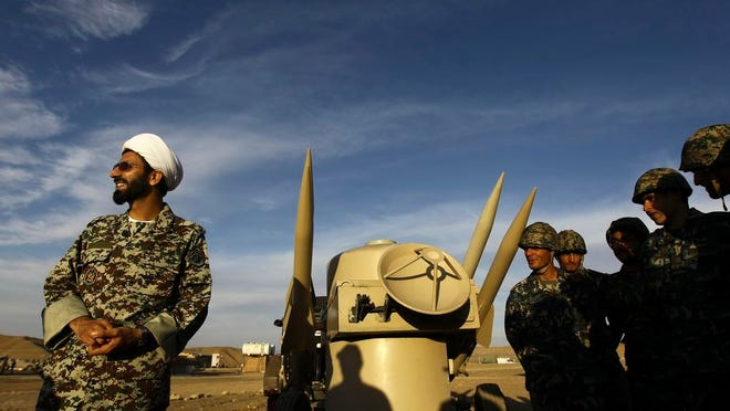 In this Nov. 13, 2012 file photo, an Iranian clergyman stands next to missiles and army troops, during a manoeuvre, in an undisclosed location in Iran. A decade-long U.N. arms embargo on Iran that bared it from purchasing foreign weapons like tanks and fighter jets expired Sunday, Oct. 18, 20202, as planned under its nuclear deal with world powers, despite objections from the United States.