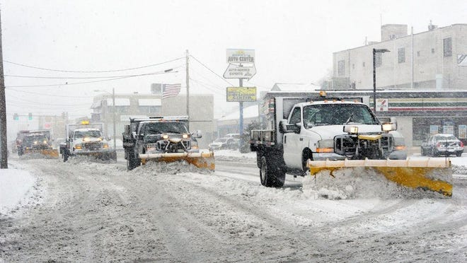 FILE - Snow plows clear the way on Belmont Street in Brockton, Tuesday, March 14, 2017.