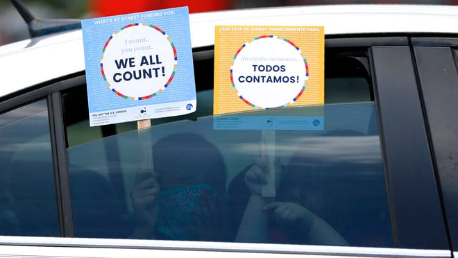 Two young children hold signs through the car window that make reference to the 2020 U.S. Census as they wait in the car with their family at an outreach event in Dallas, Thursday, June 25, 2020.