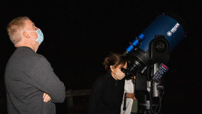 South Shore Astronomical Society vice president, Jeff Smith, stands alongside Pat Garrow, of Duxbury, as she views the Andromeda Galaxy through a 12-inch Meade telescope on Friday, October 23.