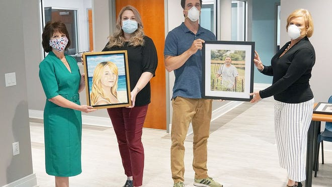 WMHS Auxiliary president Julie Davis, Sandy Arnold, Darrin Isom and auxiliary past president Sherry Schmitt hold some of the artwork that will hang in the Center for Hope and Healing.