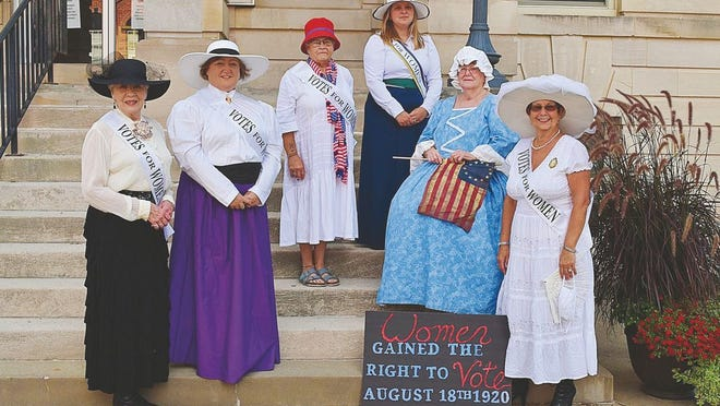 The Daughters of the American Revolution are dressed as suffragettes. Pictured from left to right are: JoAnn Rhodes Jones-Green, Debby Martin Burge, Marji Parsons, Grace Parsons Arthur, Mary Weekly Pistelli as Betsey Ross, and Selma O'Dell Humphreys.