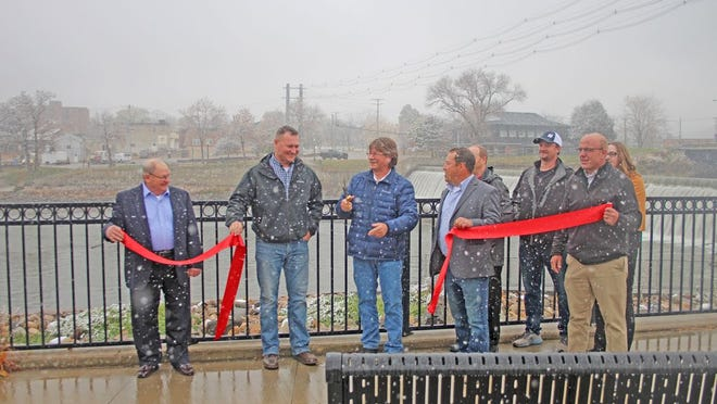 The Granite Falls Mayor Dave Smiglewski cuts the ribbon after Granite Falls was awarded $2.75 million for updates to their hydro-electric plant.