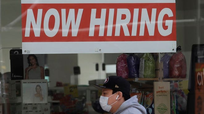 This photo shows a man wearing a mask while walking under a Now Hiring sign at a CVS Pharmacy during the coronavirus outbreak in 2020.