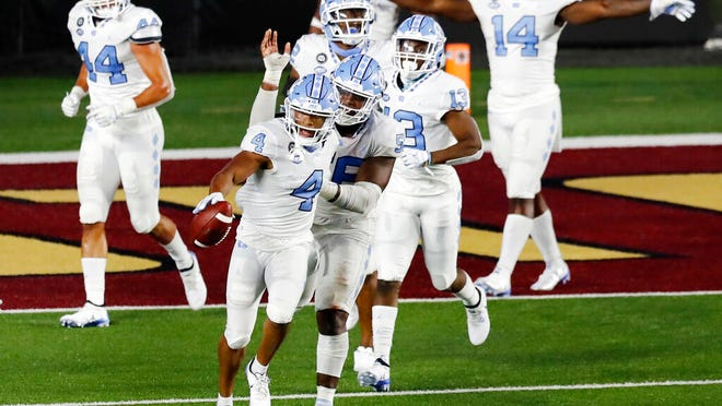 North Carolina defensive back Trey Morrison (4) celebrates after running the ball back on an interception of a two-point conversion attempt by Boston College during the second half of an NCAA college football game, Saturday, Oct. 3, 2020, in Boston.