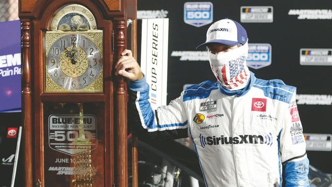 Martin Truex Jr. poses with his grandfather clock trophy after winning a NASCAR Cup Series auto race Wednesday, June 10, 2020, in Martinsville, Va.