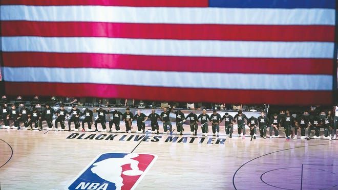 Members of the Orlando Magic and Brooklyn Nets kneel around a Black Lives Matter logo during the national anthem before the start of an NBA basketball game Friday, July 31, 2020, in Lake Buena Vista, Fla.