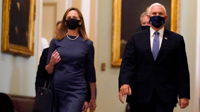 Judge Amy Coney Barrett, President Donald Trump's nominee for the U.S. Supreme Court, is escorted to the Senate by Vice President Mike Pence where she will begin a series of meetings to prepare for her confirmation hearing, at the Capitol in Washington, Tuesday, Sept. 29, 2020.