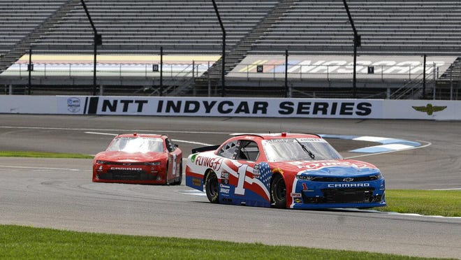NASCAR Xfinity Series driver Michael Annett leads Spartanburg's B.J. McLeod as he drives through a turn during practice for the NASCAR Xfinity Series race Friday at Indianapolis Motor Speedway in Indianapolis.