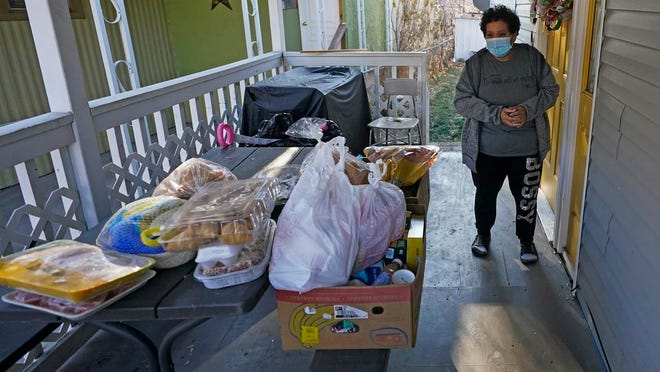 Evelyn Maysonet looks at the food delivery from the Weber-Morgan Health Department Tuesday, Nov. 24, 2020, in Ogden, Utah. Maysonet has been isolating with her husband and son in their Ogden home since all three tested positive for COVID-19 over a week ago. None of them have been able to leave home to buy groceries so Maysonet said they were thrilled to receive the health department's delivery.