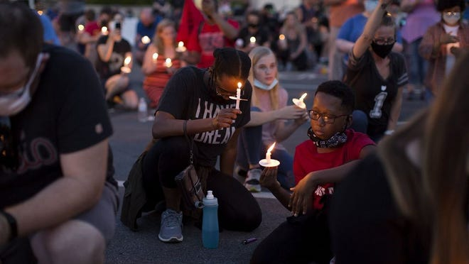 About 500 people at Gahanna City Hall kneel for 8 minutes and 46 seconds during a candlelight vigil on June 11 to remember George Floyd and other lives lost at the hands of police.
