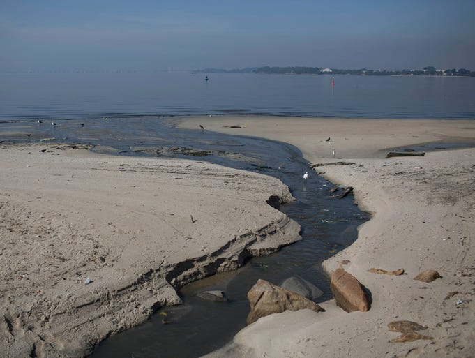 Untreated sewage creates a dark streak on the sand as it flows into the water of Guanabara Bay in Rio de Janeiro.