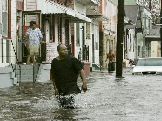 People walk streets in New Orleans flooded by Hurricane