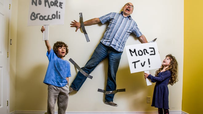 """A son and a daughter have hung their father on the wall with duct tape and keep him as a hostage while they are holding placards saying """"More TV"""" and  """"No more Broccoli"""" Credit: Getty Images"""