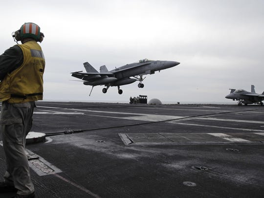 In this Feb. 13, 2012, file photo, a U.S. fighter jet lands on the USS Abraham Lincoln aircraft carrier during exercises in the Persian Gulf.