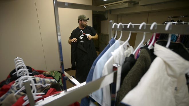 Brad Schwertz, operations manager at My Neighbor in Need, hangs up donated coats ahead of the My Student in Need coat closet launch.
