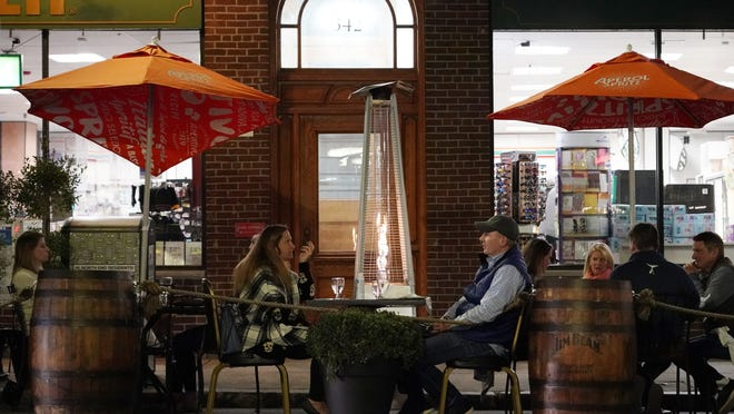 Patrons eat dinner outdoors Friday, Nov. 6, 2020, in Boston's North End. More stringent coronavirus restrictions are now in effect in Massachusetts, including requiring restaurants to stop providing table service at 9:30 p.m. Liquor sales at restaurants and package stores will also shut down at 9:30 p.m.
