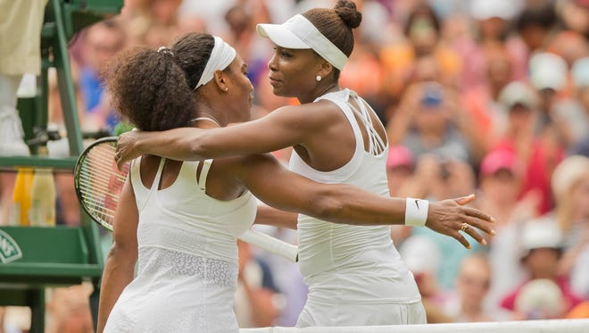 Serena Williams and Venus Williams hug at the net after their match on day seven of The Championships Wimbledon on July 5, 2015.