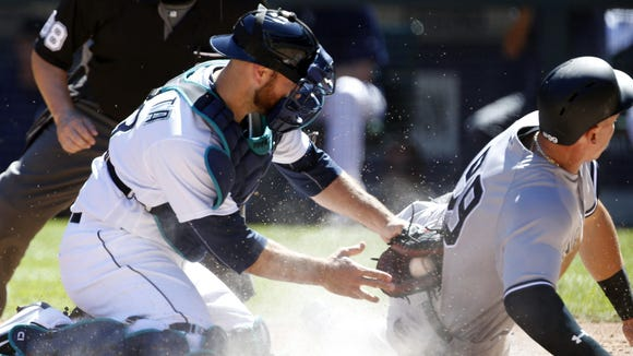 New York Yankees right fielder Aaron Judge scores before Seattle Mariners catcher Chris Iannetta can apply the tag during the second inning of the Yankees' 5-0 win at Safeco Field Wednesday afternoon.