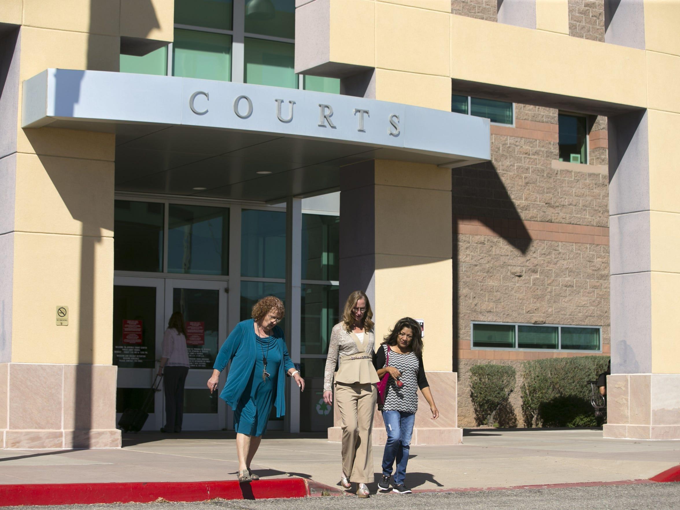 Michelle Calderon (center), of Tucson, walks out of